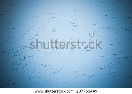 Background of water drop on  a blue metallic surface with vignette - stock photo