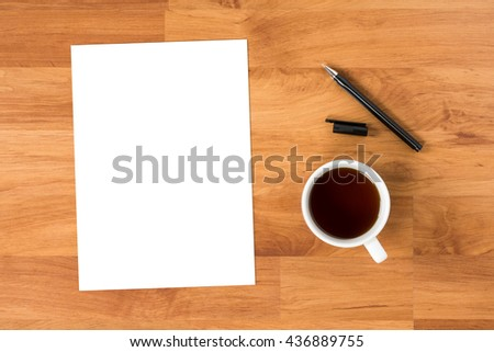 Background of wood desk table with white blank paper, coffee and pen. Top view with copy space.