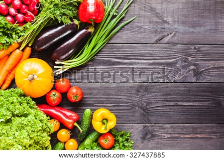 Background of wooden planks black color with fresh vegetables.