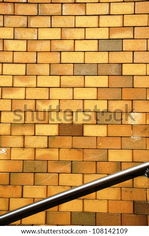 Background of yellow brick wall and steel stair railing.