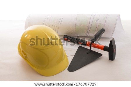 Background of yellow hardhat, hammer blue print paper plan and mason trowel isolated on white  - stock photo