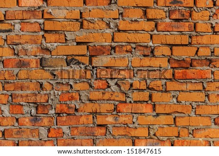 Background on the basis of a rough brickwork of cracked colored bricks.