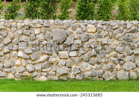 background pattern gray color of modern style design decorative fence real stone wall surface with cement on green grass field - stock photo