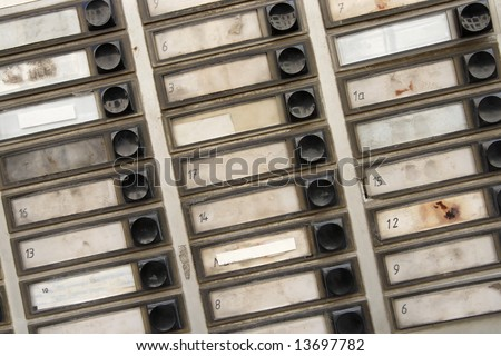 Background pattern of grungy old apartment buzzers - names removed. - stock photo