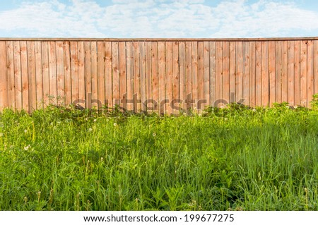 Background rustic wooden fence with green grass  in front of it and blue sky with clouds - stock photo