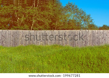 Background rustic wooden fence with green grass  in front of it and trees - stock photo