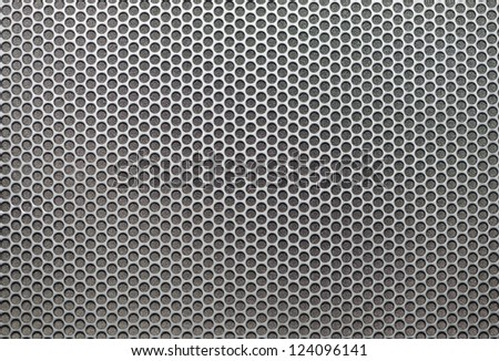 Background sheet of metal covered with lines of circular holes - stock photo