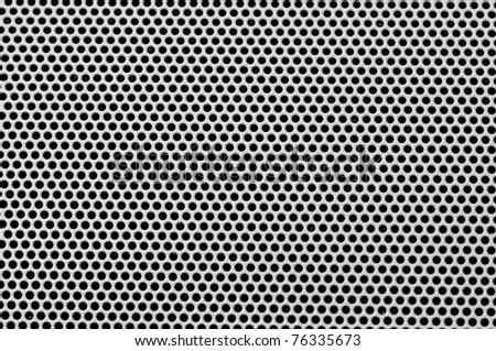 Background sheet of metal covered with lines of circular holes. - stock photo