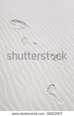 "Background shot of footprints in pristine, wind blown white beach sand. Good ""shifting sands of time"" concept. - stock photo"