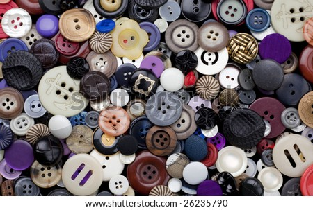 Background surface filled with a variety of dress-maker and clothing buttons, many of them vintage. - stock photo