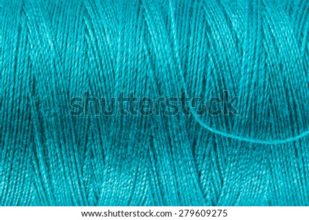 Background texture and macro view of petrol blue sewing yarn.