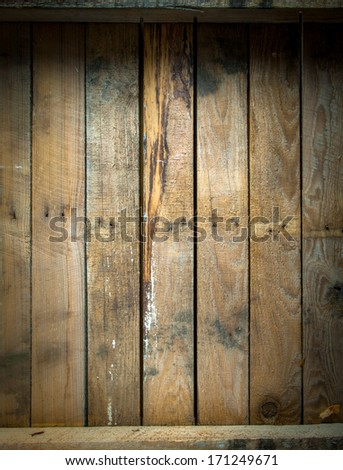 Background texture of a grungy stained and weathered wooden table top with a line of old nails and parallel vertical planks - stock photo