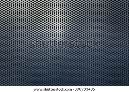Background texture of a perforated silver metal grid with a highlight and shadows graduating to dark grey, full frame