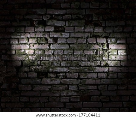 Background Texture of abandoned old red Brick wall covered with green moss growing out of it at Fort with light circle gradient and dark frame - stock photo