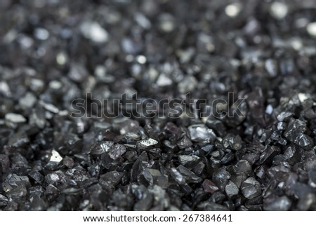 Background texture of an asphalt or tarmac road surface showing the tiny stones in the gravel with shallow dof - stock photo