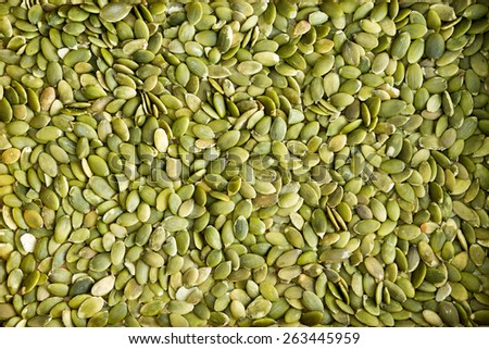 Background texture of fresh healthy green de-husked pumpkin seeds a popular snack and salad ingredient rich in protein and nutrients - stock photo
