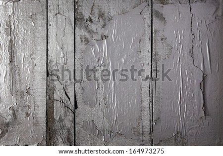 Background texture of grunge peeling weathered paint on cracked wooden boards