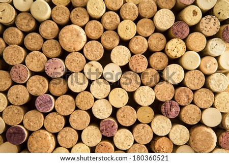 Background texture of neatly arranged corks from wine and champagne bottles packed tightly together with their tops facing up to the camera forming a circular pattern - stock photo
