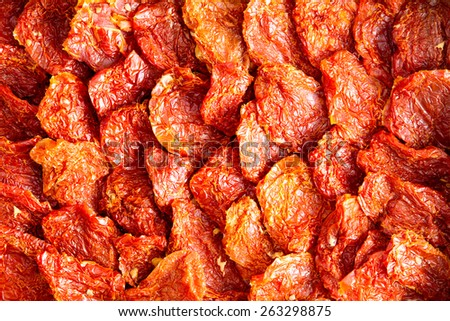 Background texture of neatly arranged ripe red sun dried tomatoes, a healthy snack and appetizer rich in antioxidants and vitamins - stock photo