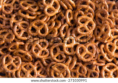 Background texture of salted savory mini pretzels in the traditional looped knot shape in a random heap viewed full frame from overhead - stock photo