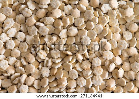 Background texture of small oven-baked oyster crackers usually served with soup in a full frame closeup view from above - stock photo
