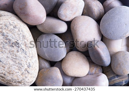 Background texture of smooth oceanic stones eroded by the force of the tides and currents to a rounded form before being deposited on the seashore - stock photo