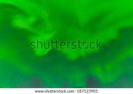 Background texture pattern abstract of green Aurora borealis or northern lights bands on night sky full of stars - stock photo
