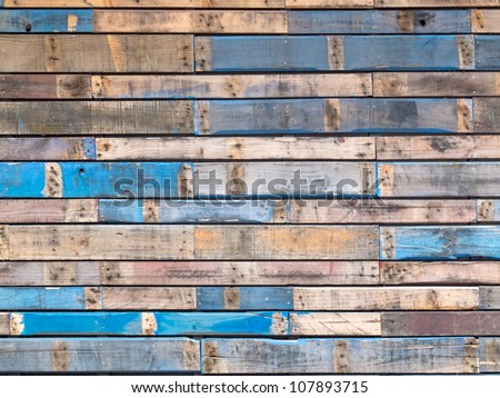 Background texture pattern of weathered wooden planks with grungy remnants of blue paint forming the siding of an exterior building wall - stock photo