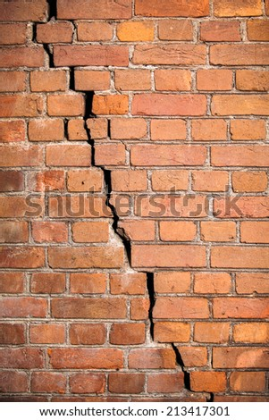 Background texture. The wall of the old red brick with a crack across the wall