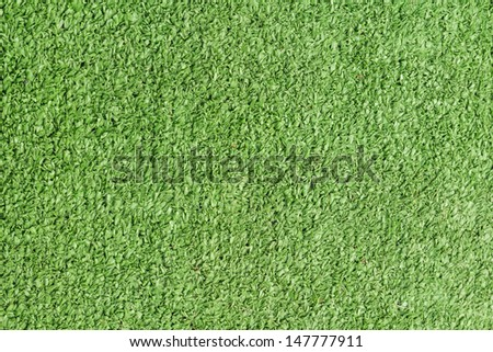 Background texture with fake grass in a public children playground, top view - stock photo