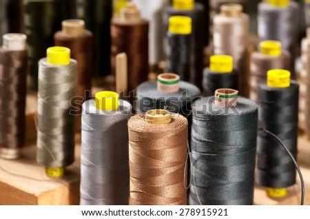 Background view of various colored yarns on bobbins at a tailor or clothing design studio in shades of grey and brown with focus to one in the foreground - stock photo