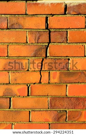 Background with a crack in a red brick wall