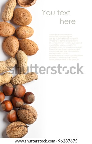 Background with assorted nuts almond, hazelnut, walnut and peanut over white with sample text - stock photo