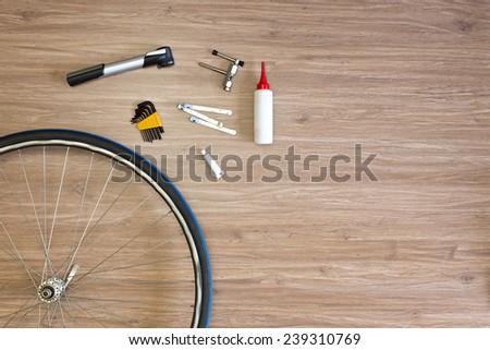 Background with bicycle tools laid out on a wooden floor, with a spoked wheel, tire levers, a pump, glue and a chain punch. Items, used to repair a flat tire - stock photo
