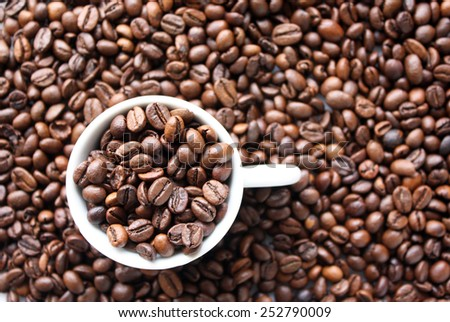 Background with coffee beans and cup full of coffee beans - stock photo