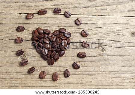Background with coffee beans in shape of hearts on old wooden table, top view - stock photo