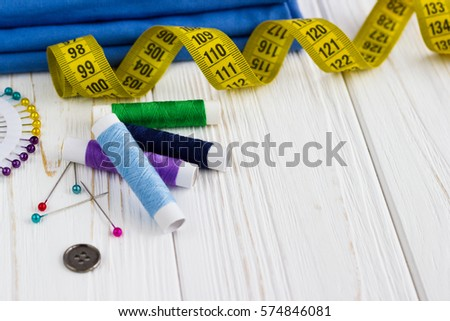background with color threads, meter, buttons,pins and blue textile