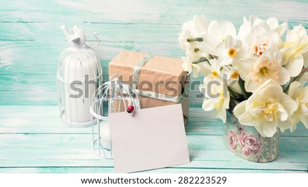 Background with colorful narcissus flowers , candles, box with present  and empty tag for text on turquoise painted wooden planks. Selective focus. Place for text. Toned image. - stock photo