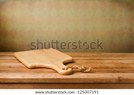 Background with cutting board on wooden table over vintage wallpaper - stock photo