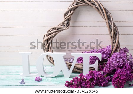 Background with decorative heart, word love  and  lilac flowers  on  wooden planks. Selective focus.  - stock photo