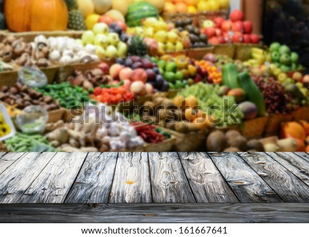Background with empty wooden table and blured fruits and vegetables - stock photo