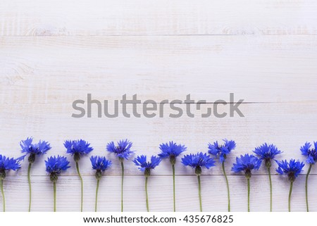 Background with  fresh cornflowers on a light wooden table background. Place for text.Selective focus. - stock photo