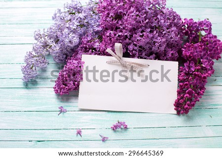 Background  with fresh lilac flowers and empty tag on turquoise painted wooden planks. Selective focus. Place for text.  - stock photo
