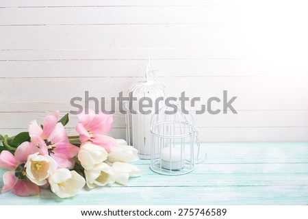 Background with fresh spring flowers and candles in ray of light on turquoise painted planks against white wall. Selective focus. Place for text. - stock photo