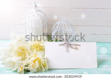 Background with fresh spring flowers, tag and candles in decorative bird cages in ray of light on turquoise painted planks against white wall. Selective focus is on tag.  - stock photo