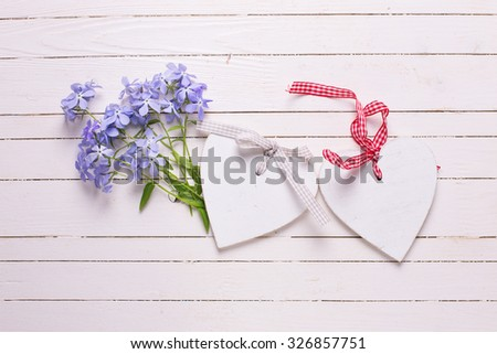 Background with fresh tender blue flowers and decorative hearts on white painted wooden planks. Selective focus. Place for text.
