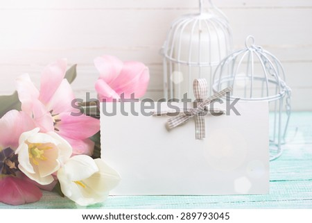 Background with fresh tulips and empty tag for your text  in ray of light on turquoise painted planks against white wall. Selective focus. - stock photo
