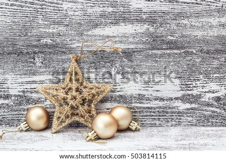 Background with golden Christmas decorations - star and small balls, on gray wooden boards. Space for text.