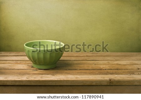 Background with green bowl on wooden table over green wall - stock photo