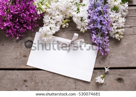 Background with  lilac flowers  and empty tag on vintage wooden table. Selective focus. Place for text.